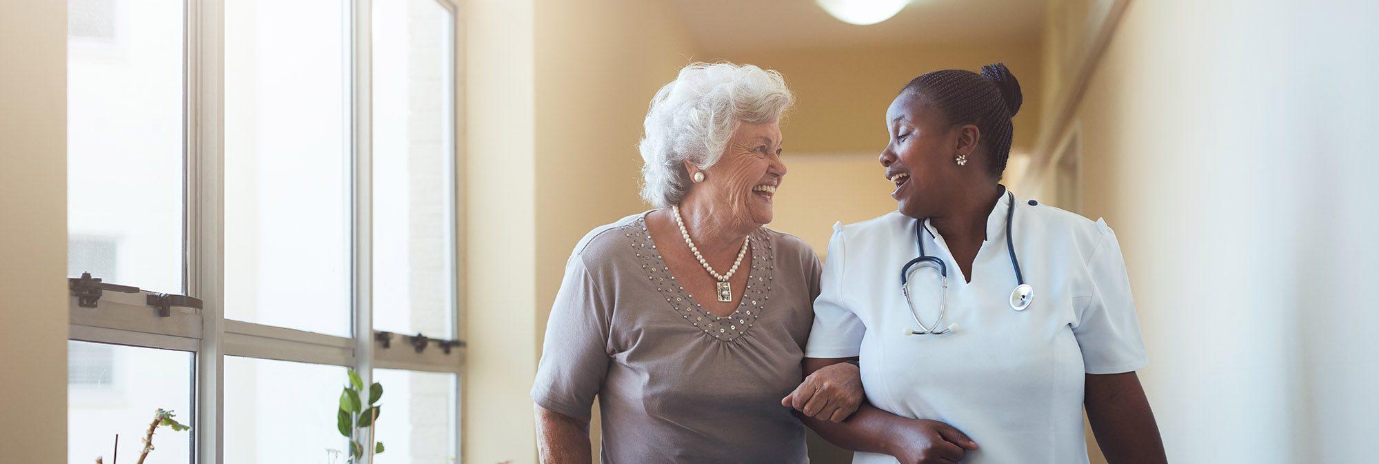 nurse walking down a hallway with an elderly patient