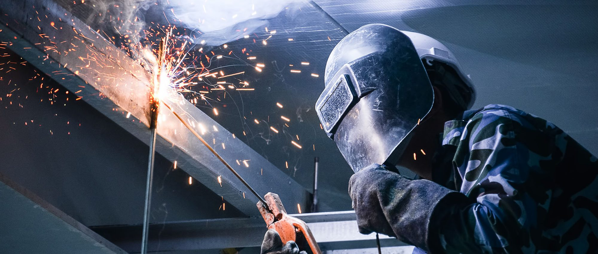 photo of person welding in a high space