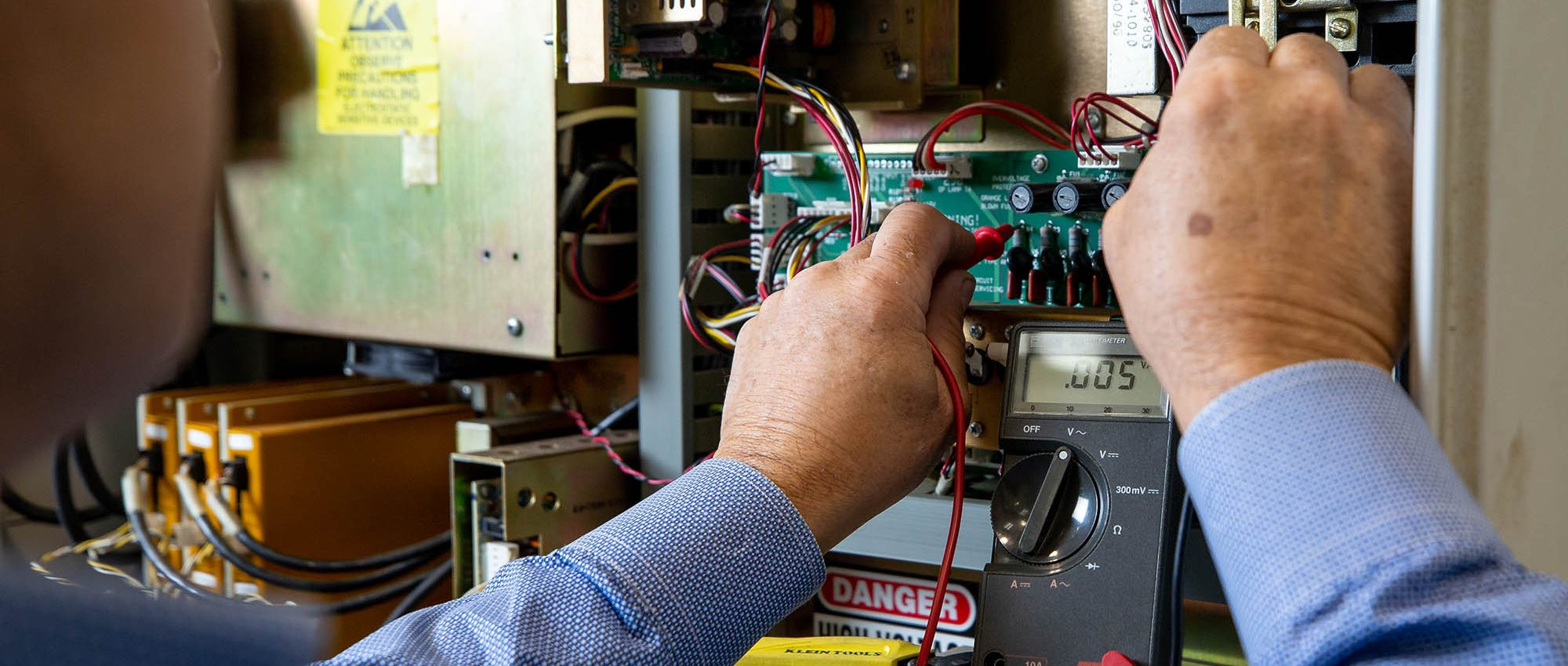 picture of an industrial maintenance technician using an ohm meter