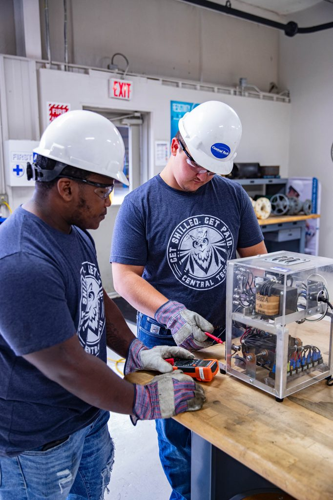 Pipeline students taking an output voltage reading on a rectifier at Central Tech