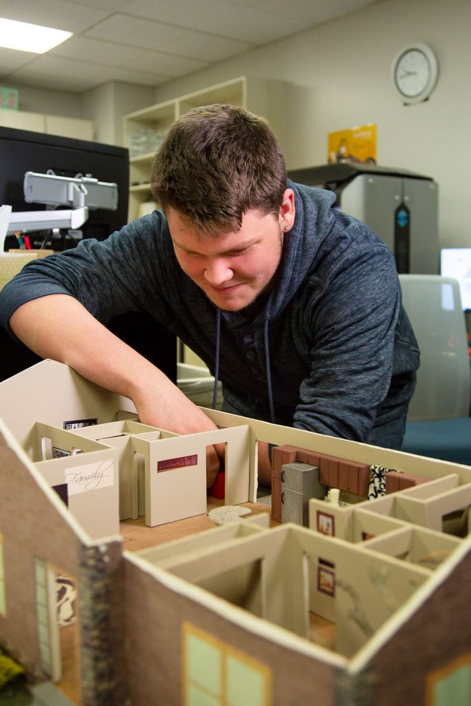 photo of a drafting student looking at a house model