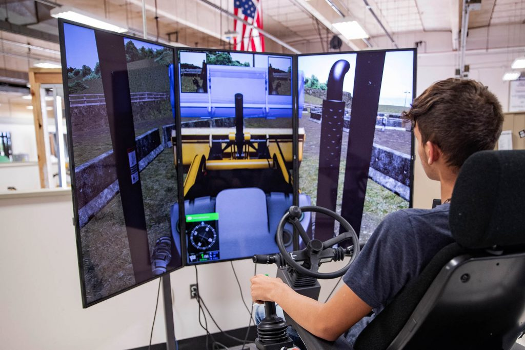 student operating a heavy equipment simulator