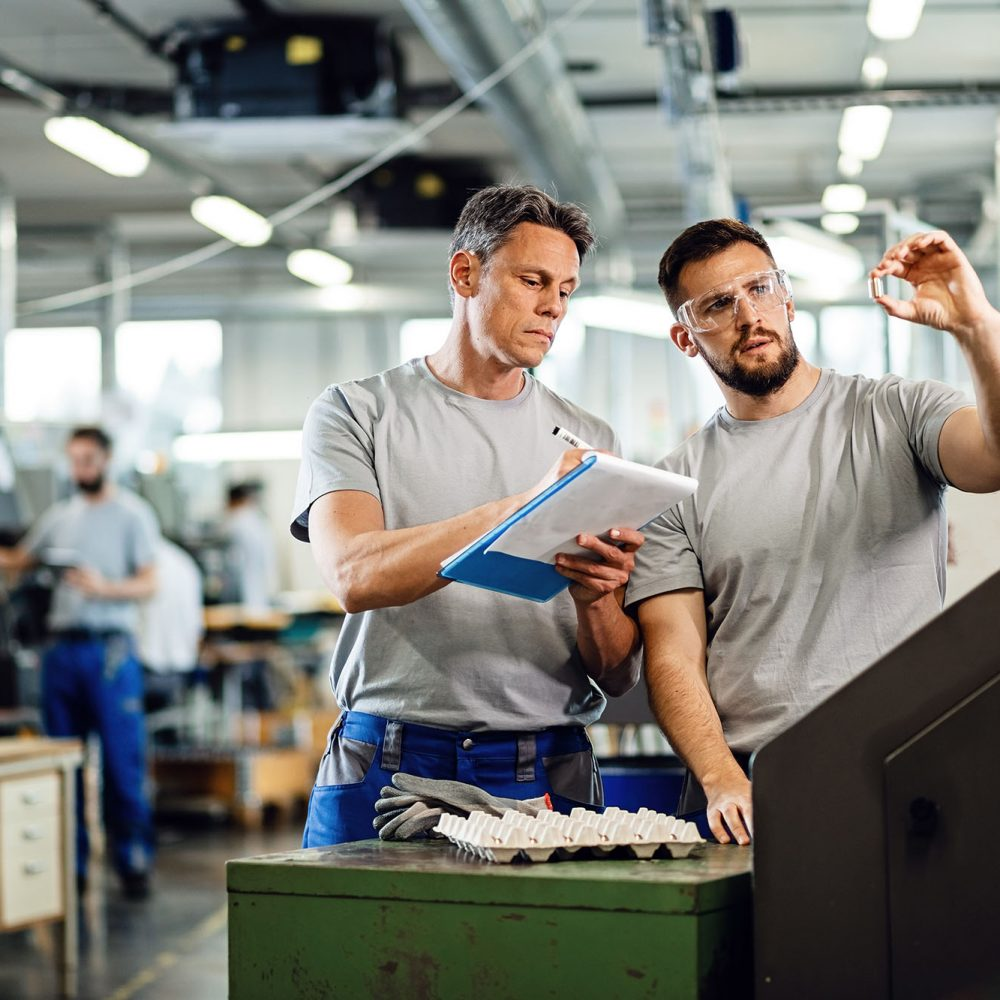 two men talking on a manufacturing floor